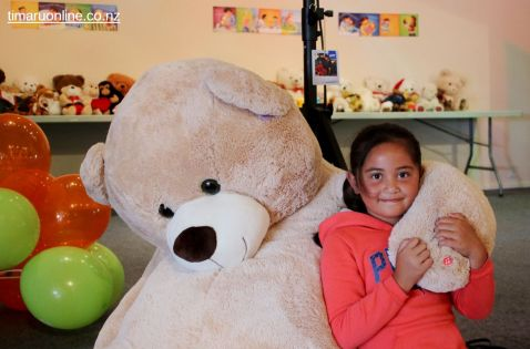 "Sharyssa Wilson-Matthews (7) gets a cuddle from ""Teddy"""
