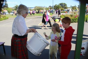 Pauline Roberts from the Timaru Scottish Society Pipe Band gives Grace & Zavier a go on the drums