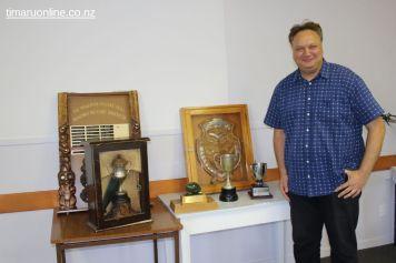 Rino Tirikatene (MP for Te Tai Tonga) stands beside the Tirikatene Shield and other tournament taonga
